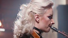 Retrato del primer de un músico de sexo femenino que realiza una canción en un saxofón almacen de metraje de vídeo