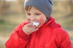 Retrato del primer de un muchacho emocional que come el helado foto de archivo