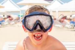 Retrato del primer de un muchacho de risa feliz con la máscara del salto en una playa soleada Foto de archivo libre de regalías