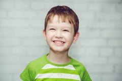Retrato del primer de un muchacho sonriente en un fondo ligero Foto de archivo libre de regalías