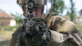 Retrato del primer de un punto de defensa del soldado joven en una zona rural con el edificio arruinado en el fondo almacen de metraje de vídeo