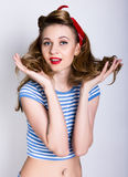 Retrato del primer de un rubio hermoso en una camisa rayada y una bufanda roja, ella apoya su pelo rizado de las manos Pin para a Imagenes de archivo