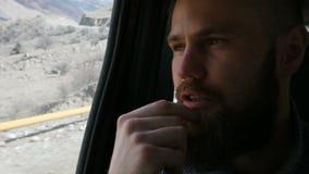Retrato del primer de un varón barbudo del inconformista que habla que se sienta en el coche en el asiento trasero y que reflexio almacen de metraje de vídeo