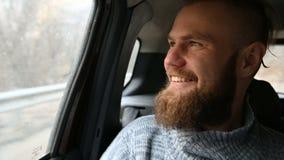 Retrato del primer de un varón barbudo de risa del inconformista que se sienta en un coche en el asiento trasero y que medita mie almacen de metraje de vídeo