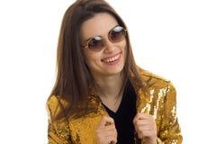 Retrato del primer de una chica joven atractiva en una chaqueta brillante y vidrios Fotos de archivo