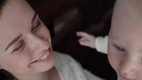 Retrato del primer de una madre hermosa que sonr?e con el beb? en cama almacen de metraje de vídeo