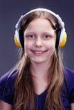 Retrato del primer de una muchacha adolescente sonriente con los auriculares Foto de archivo