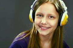 Retrato del primer de una muchacha adolescente sonriente con los auriculares Imágenes de archivo libres de regalías