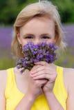 Retrato del primer de una muchacha en flores púrpuras al aire libre en verano Imagen de archivo libre de regalías