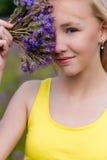 Retrato del primer de una muchacha en flores púrpuras al aire libre en verano Imagenes de archivo