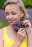Retrato del primer de una muchacha en flores púrpuras al aire libre en verano Foto de archivo libre de regalías