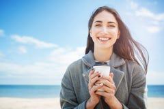 Retrato del primer de una muchacha sonriente que sostiene la taza para llevar Fotos de archivo