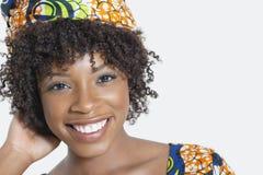Retrato del primer de una mujer afroamericana que sonríe sobre fondo gris Imagen de archivo