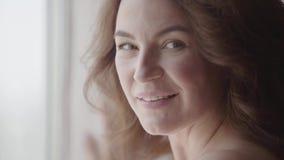 Retrato del primer de una mujer bastante madura que mira la cámara Sun brilla en ella de la ventana Mujer cauc?sica feliz almacen de video