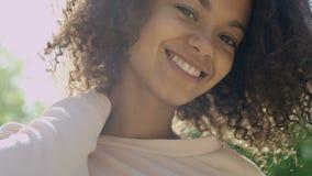 Retrato del primer de una mujer hermosa de la raza mixta que sonríe con gusto a una cámara almacen de video