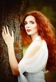 Retrato del primer de una mujer hermosa del jengibre cerca del árbol Imágenes de archivo libres de regalías