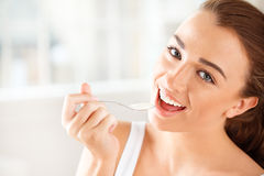 Retrato del primer de una mujer joven atractiva que come el yogur Foto de archivo