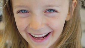 Retrato del primer de una niña feliz que estalla en risa lentamente almacen de metraje de vídeo
