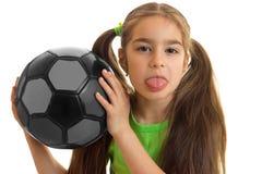 Retrato del primer de una niña que sostiene la bola y muestra lengua Foto de archivo libre de regalías