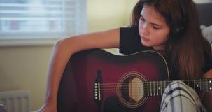 Retrato del primer de una señora joven en su sitio usando una guitarra de jugarla, muy curiosamente, que usa un cuaderno para tom almacen de metraje de vídeo