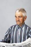 Retrato del primer de una situación y de una lectura del hombre mayor un newspap Fotos de archivo libres de regalías