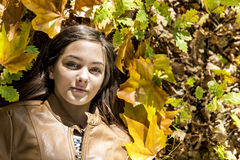 Retrato del primer del adolescente precioso que miente el otoño caido Imagen de archivo
