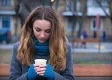 Retrato del primer del café de consumición de la mujer joven en el parque Fotografía de archivo libre de regalías