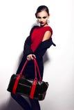 Retrato del primer del encanto del modelo caucásico moreno elegante atractivo hermoso de la mujer joven en vestido rojo con b negr foto de archivo