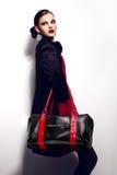 Retrato del primer del encanto del modelo caucásico moreno elegante atractivo hermoso de la mujer joven en vestido rojo con b negr foto de archivo libre de regalías
