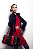 Retrato del primer del encanto del modelo caucásico moreno elegante atractivo hermoso de la mujer joven en vestido rojo con b negr imagenes de archivo