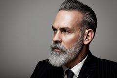 Retrato del primer del hombre de negocios adulto serio que lleva el traje de moda contra la pared vacía horizontal Fotos de archivo libres de regalías