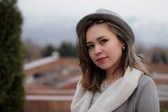 Retrato del primer del invierno de una señora linda en capa y bufanda grises que da un paseo en el parque Fotos de archivo