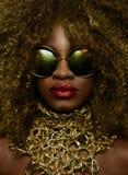 Retrato del primer del modelo femenino afroamericano de oro mágico en gafas de sol masivas con maquillaje brillante del brillo, b Fotos de archivo