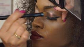 Retrato del primer del modelo femenino negro atractivo con maquillaje brillante en estudio almacen de video