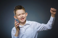 Retrato del primer del muchacho feliz con el móvil o del teléfono celular en fondo gris Foto de archivo