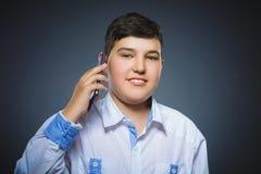 Retrato del primer del muchacho feliz con el móvil o del teléfono celular en fondo gris Imagen de archivo