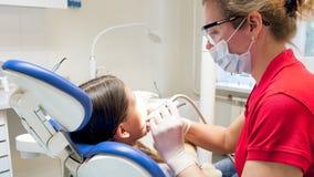 Retrato del primer del dentista que trata los dientes de las muchachas con el taladro dental Foto de archivo libre de regalías