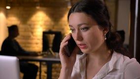 Retrato del primer del empleado de sexo femenino bonito joven que tiene una conversación sobre el teléfono que se sienta delante  imagenes de archivo