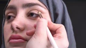 Retrato del primer en el perfil de las manos femeninas que hacen maquillaje del ojo con el lápiz y el cepillo marrones para la mu metrajes
