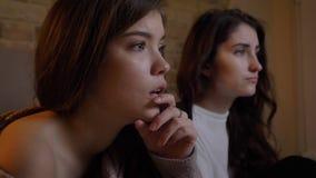 Retrato del primer en el perfil de las muchachas caucásicas jovenes asustadas que ven la TV seriamente en fondo casero acogedor metrajes