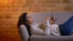 Retrato del primer en perfil de la empresaria morena atractiva que se relaja en el sofá y que mira en la tableta en casa almacen de metraje de vídeo