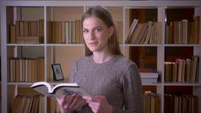 Retrato del primer del estudiante atractivo joven que lee un libro y que sonríe feliz mirando la cámara en la universidad metrajes