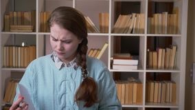 Retrato del primer del estudiante bonito joven que toma las notas que miran la cámara en la biblioteca de universidad dentro almacen de metraje de vídeo