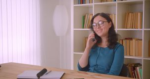 Retrato del primer del estudiante caucásico bonito joven en vidrios que estudia y que tiene una llamada de teléfono que habla ale almacen de video