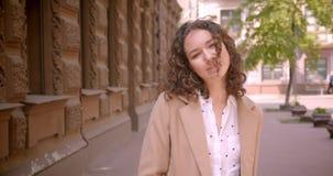 Retrato del primer del estudiante caucásico joven que sonríe feliz presentando delante de la cámara que se coloca al aire libre e almacen de metraje de vídeo