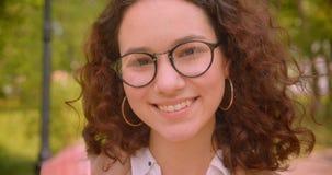 Retrato del primer del estudiante caucásico rizado de pelo largo joven en vidrios que sonríe feliz mirando la cámara almacen de metraje de vídeo
