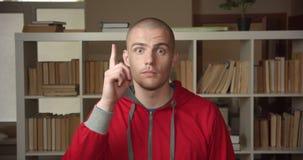 Retrato del primer del estudiante masculino caucásico atractivo joven que cabecea diciendo sí la mirada de la cámara en la biblio metrajes