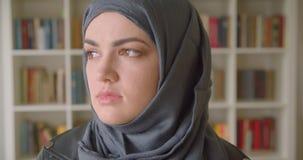 Retrato del primer del estudiante musulmán atractivo joven en el hijab que da vuelta y que mira a la cámara en la biblioteca de u almacen de metraje de vídeo