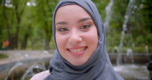 Retrato del primer del estudiante musulm?n bonito en hijab que sonr?e sinceramente y con mucho gusto que se coloca cerca de la fu almacen de video