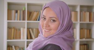 Retrato del primer del estudiante musulmán bonito joven en el hijab que da vuelta y que mira a la cámara que sonríe feliz en bibl metrajes